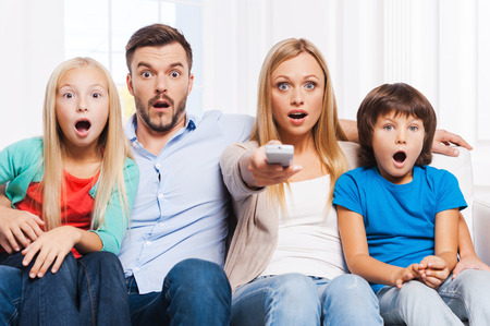 That is just amazing! Surprised family of four bonding to each other and keeping mouth open while watching TV at home together photo