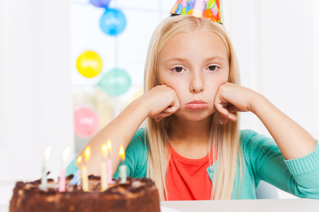 lonely girl: Feeling lonely at her party. Happy little girl looking at the birthday cake and smiling