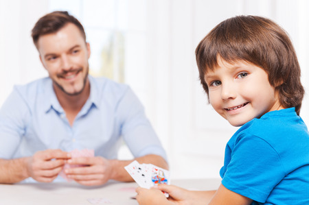 Enjoying free time together. Happy father and son playing cards and smiling photo