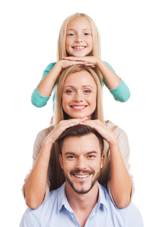 caucasian white: We are family! Happy family of three leaning at each other head and smiling while standing against white