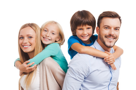 famiglia: Felice di essere una famiglia. Happy family di quattro incollaggio a vicenda e sorridente in piedi contro il bianco