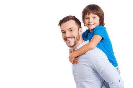 Vader en zoon. Zijaanzicht van de gelukkige vader die zijn zoon op de rug en glimlachend terwijl zowel staande geïsoleerd op wit Stockfoto