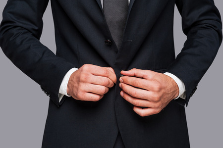 man in suit: Making business look good. Close-up of man buttoning his jacket while standing against grey background