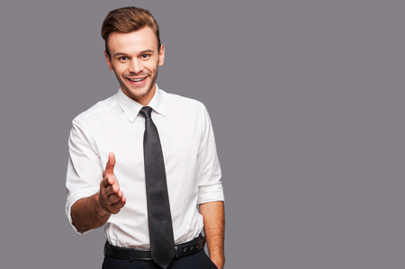 hands on waist: You are welcome in our company! Portrait of cheerful young man in formalwear stretching out hand for shaking while standing against grey background