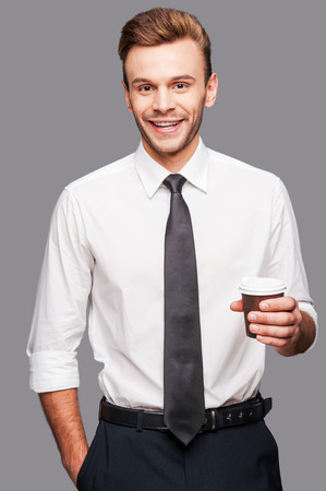 Coffee and work.  Cheerful young man holding a cup of coffee while standing against grey background photo
