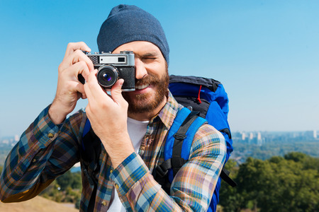 Can not miss such beautiful scenery. Handsome young man carrying backpack and taking a picture of a view photo