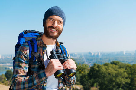 Good scenery. Handsome young man carrying backpack and looking at camera with smile while standing in the nature and holding binoculars