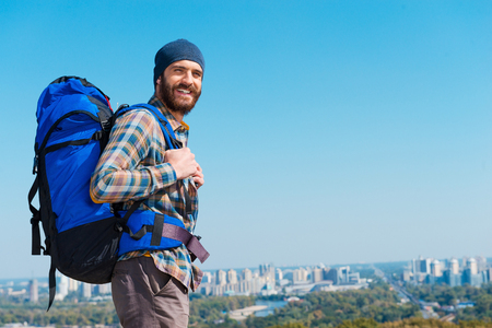 one young man: In a search of adventures. Handsome young man carrying backpack and looking at camera through the shoulders a with smile