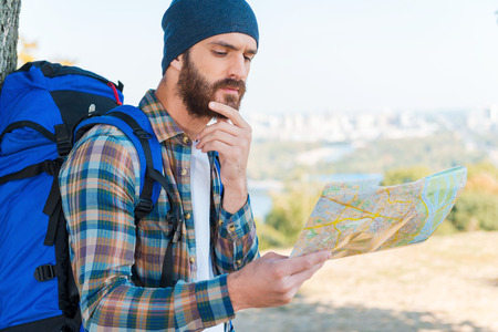There is no this place on the map. Thoughtful young man carrying backpack and looking through a map photo