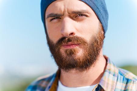 hombre con barba: Confiado guapo. Retrato del hombre barbudo hermoso que mira a la cámara mientras está de pie al aire libre Foto de archivo