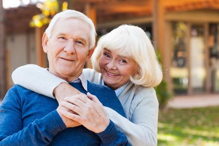 personas abrazadas: Feliz pareja senior. Feliz pareja senior de uni�n entre s� y sonriendo mientras est� de pie al aire libre y en el frente de su casa