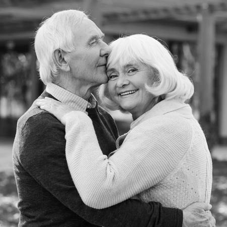 bonhomme blanc: Portrait d'un amour infini. Portrait en noir et blanc du couple heureux liaison principal � l'autre et souriant tout en se tenant � l'ext�rieur et en face de leur maison Banque d'images
