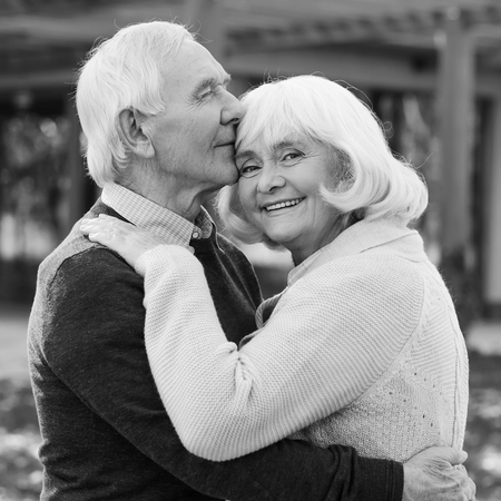 ojos negros: Retrato de amor sin fin. Retrato blanco y negro de la pareja feliz uni�n mayor entre s� y sonriendo mientras est� de pie al aire libre y en el frente de su casa
