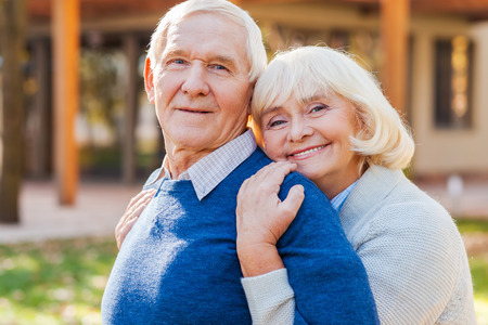 safe house: Feeling safe near him. Happy senior couple bonding to each other and smiling while standing outdoors and in front of their house