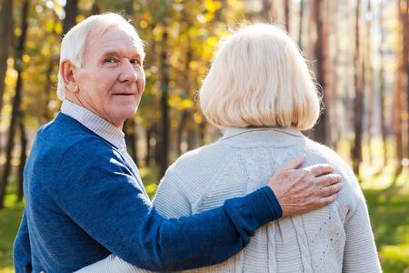 persona caminando: Amo a mi esposa. Vista trasera del hombre mayor feliz mirando por encima del hombro y sonriendo mientras caminaba por el parque con su esposa Foto de archivo