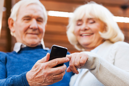 good news: Good news. Happy senior couple bonding to each other and smiling while standing outdoors and looking at the mobile phone Stock Photo