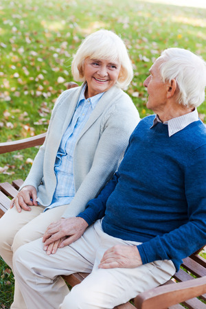 white people: Relaxing in park together. Top view of happy senior couple holding hands and looking at each other while sitting on the bench in park together Stock Photo