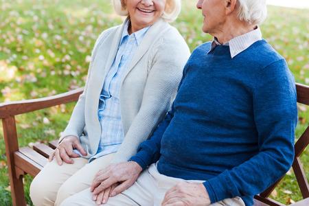 cogidos de la mano: Disfrutando de su tiempo juntos. Primer plano de la feliz pareja de ancianos cogidos de la mano y mirando el uno al otro mientras est� sentado en el banco en el parque juntos Foto de archivo