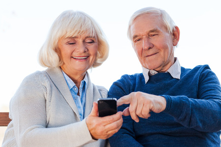 easier: Technologies become easier. Cheerful senior couple looking at the mobile phone and smiling while sitting on the park bench together Stock Photo