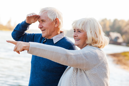 Look over there! Happy senior couple standing on the quayside together while woman pointing away and smiling photo