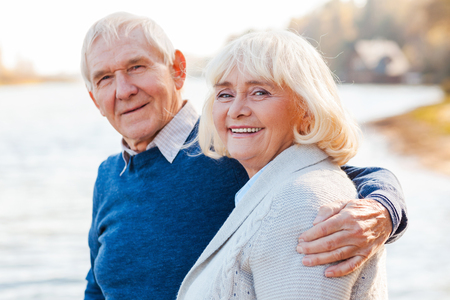 heterosexual couple: We are happy together. Happy senior couple bonding to each other and smiling while standing on the quayside together Stock Photo