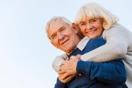 personas abrazadas: Joven para siempre. �ngulo de visi�n baja de la feliz pareja senior de uni�n entre s� y sonriendo con el cielo azul como fondo