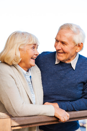 Enjoying life together. Happy senior couple looking at each other and smiling while standing outdoors photo
