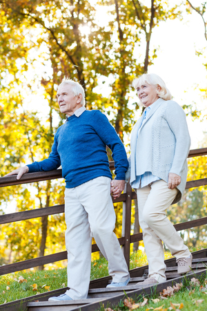 moving down: Confident senior couple. Full length of happy senior couple holding hands and moving down by wooden staircase Stock Photo