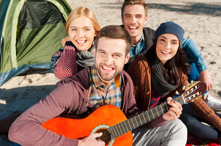 Having fun together. Top view of four young happy people sitting near the tent together while young handsome man playing guitar and smiling photo