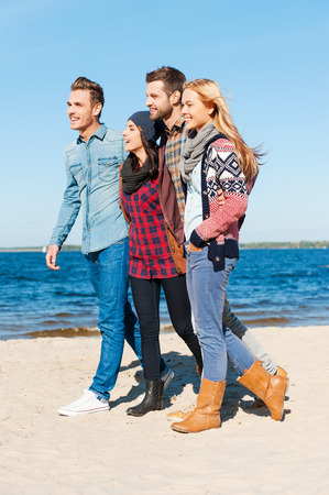 living moment: Living in the moment. Side view of four young happy people bonding to each other and smiling while walking by the beach together Stock Photo