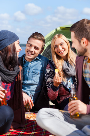 Spending great time together. Group of young cheerful people\ drinking beer and talking while camping at the riverbank