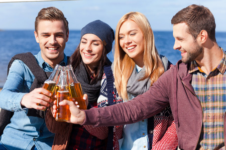 Cheers to friendship! Four young happy people cheering with beer and smiling while bonding to each other