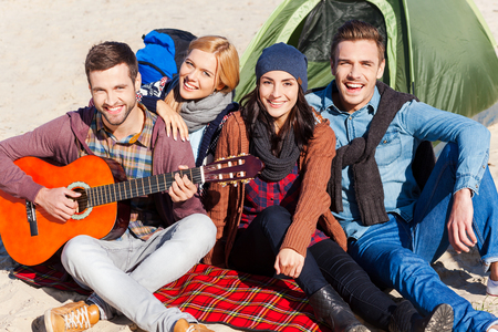 Nothing but the best friends. Top view of four young happy people sitting near the tent together while young handsome man playing guitar and smiling photo