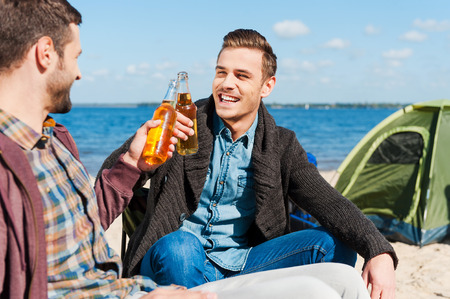 beer bottle: Cheers! Two happy men cheering with beer and smiling while sitting near the tent together Stock Photo