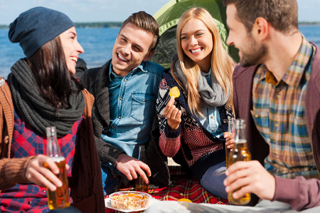 Spending time with friends. Group of young cheerful people drinking beer and talking while camping at the riverbank photo