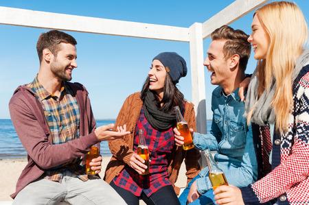 hombre tomando cerveza: Joven y despreocupada. Cuatro amigos felices hablando el uno al otro y sonriendo mientras est� sentado en la playa y bebiendo cerveza