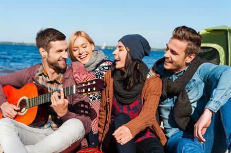 recreational pursuits: Just friends and guitar. Group of young cheerful people sitting at the riverbank together while young handsome man playing guitar and smiling