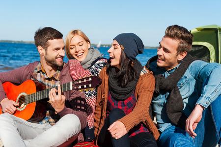 amicizia: Solo amici e chitarra. Gruppo di giovani allegri seduti sulla sponda del fiume insieme mentre bel giovane a suonare la chitarra e sorridente