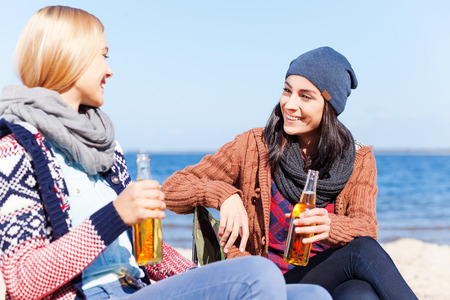 Friendly talk. Two beautiful young women drinking beer and talking to each other while sitting on the beach together photo
