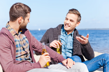 Taking time to talk with friend. Two handsome young men drinking beer and talking to each other while sitting on the beach together photo