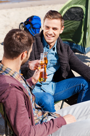 Cheers to friendship! Top view of two handsome young men cheering with beer and smiling while sitting near the tent and on the sand photo