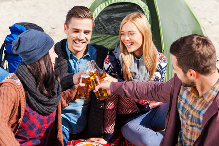 near beer: Cheers to us! Top view of four young happy people cheering with beer and smiling while sitting near the tent together Stock Photo