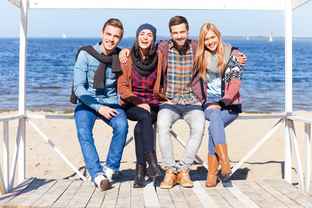 happy young man: We are always together. Full length of four young happy people bonding to each other and smiling while sitting on the beach