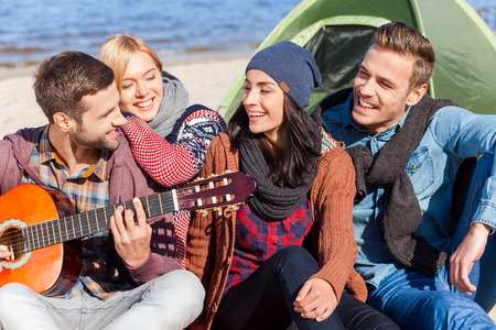 Group of young cheerful people sitting at the riverbank together while young handsome man playing guitar and smiling photo