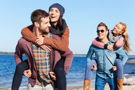 focus group: Young and carefree. Two beautiful young couples walking by the beach and smiling