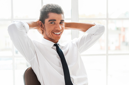 Make a small pause in your work! Handsome young Afro-American man in shirt and tie holding hands behind head and smiling while sitting at his working place photo