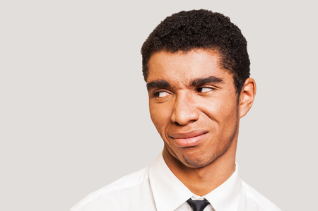 Man in disbelief.  Close-up portrait of young Afro-American man showing the disgust on his face while standing against grey background photo