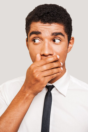 Did I say something wrong? Shocked young Afro-American man in formalwear covering mouth with hand and looking away while standing against grey background photo
