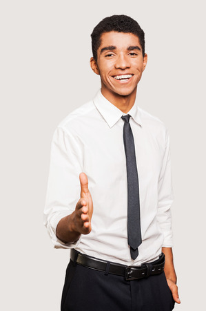 our company: You are welcome in our company! Portrait of cheerful young Afro-American man in formalwear stretching out hand for shaking while standing against grey background Stock Photo