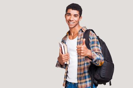 college student: Being a student is cool! Handsome young Afro-American student holding books and stretching out hand with thumb up while standing against grey background